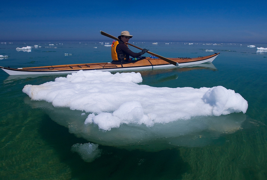 A sea kayaker paddles through ice floating in Lake Superior at Pictured Rocks National Lakeshore near Munising, Michigan.