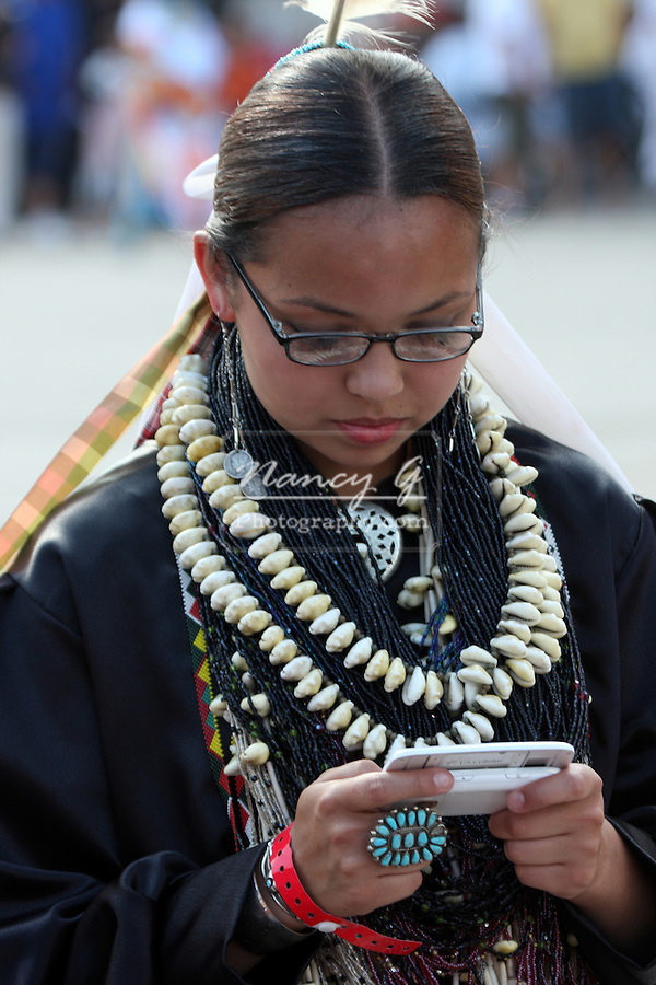 A young teenager Native American Indian women checking her texting on a cell phone at a Pow Wow at the Milwaukee Lakefront Indian Summer Festival, Wisconsin