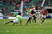 Billy Odhiambo of Kenya breaks through the tackles of Seabelo Senatla (left) and Justin Geduld of South Africa during Day Two of the iRB Marriott London Sevens at Twickenham on Sunday 11th May 2014 (Photo by Rob Munro)