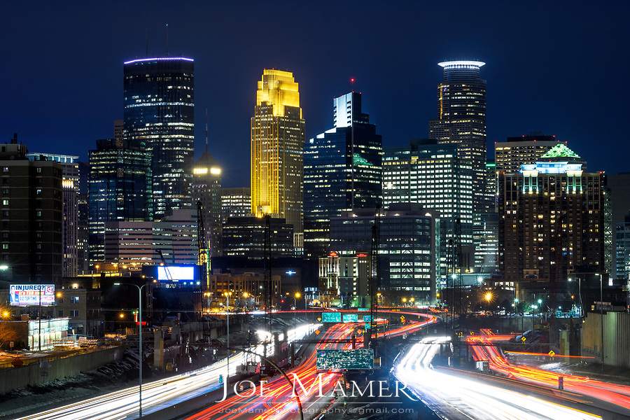 Light trails and the Minneapolis, Minnesota skyline at dusk as seen from the 24th Street walking bridge over Interstate 35W.