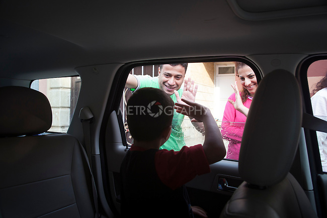 31/10/14. Erbil, Iraq. Milad waves goodbye to his uncle Amir (left) and aunt Susan from inside his uncle Salam's car.