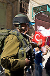 An Israeli soldier prevents the passage of Palestinian children carrying a coffin bearing the Turkish flag to commemorate those killed during the Israeli raid on the Mavi Marmara aid ship during a demonstration against the closure of Shuhada Street to Palestinians in the city of Hebron on 05.06.2010