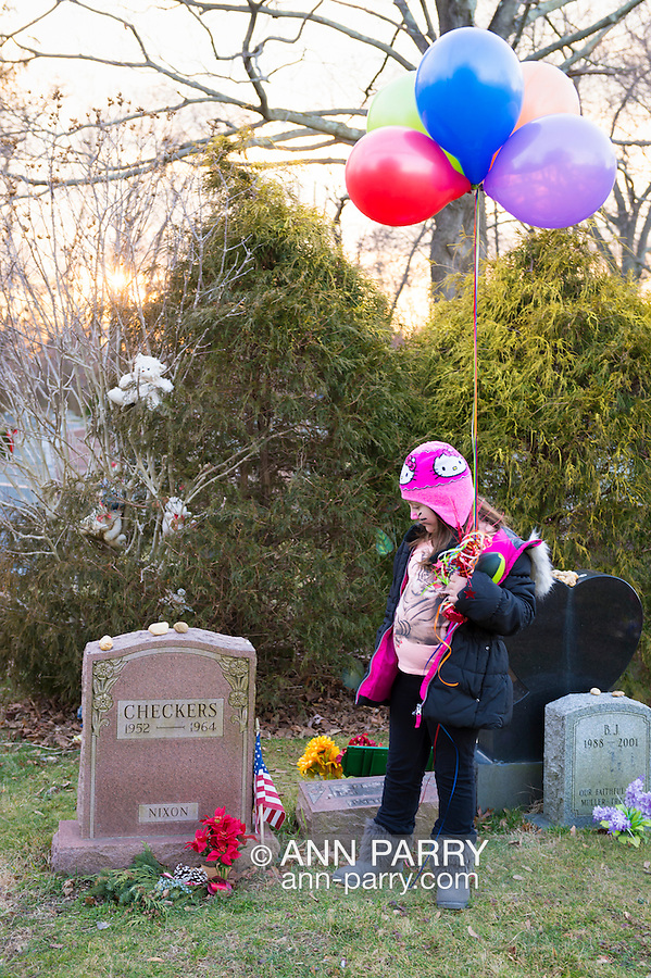 Wantagh, New York, USA. February 5, 2017.  AYLA SHAH, 6 1/2, of Merrick, looks at gravestone of CHECKERS (1952 - 1964), President Richard Nixon's pet dog, who is buried in Bide-a-Wee Pet Memorial Park cemetery outside office of Last Hope Animal Rescue. Tombstone is red granite, and small American Flag is at its side. Ayla is holding colorful helium balloons from Last Hope's Open House.