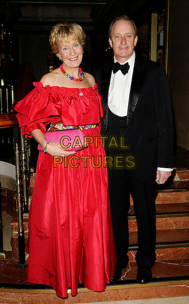 CHRISTINE HAMILTON & NEIL HAMILTON .Inside Arrivals - The Spirit of Cuba Ball, .London Hilton Park Lane Hotel, London, England, November 15th 2008..full length red dress long of the shoulder black suit tuxedo bow tie pink clutch bag married husband wife  .CAP/CAN.©Can Nguyen/Capital Pictures
