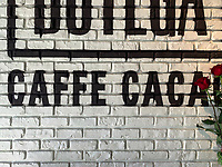 Switzerland. Canton Ticino. Lugano. Botega Caffe Cacao. Sign on an old brick wall. Red roses on Valentine's day. 14.02.2019 © 2019 Didier Ruef