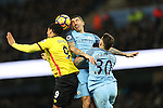 Aleksandar Kolarov and Nicolas Otamendi of Manchester City jump for the ball with Troy Deeney of Watford during the English Premier League match at The Etihad Stadium, Manchester. Picture date: December 12th, 2016. Photo credit should read: Lynne Cameron/Sportimage
