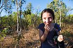 A young girl tasting ascorbic acid from green weaver ants in the Kimberley, Vansittart Bay, Australia