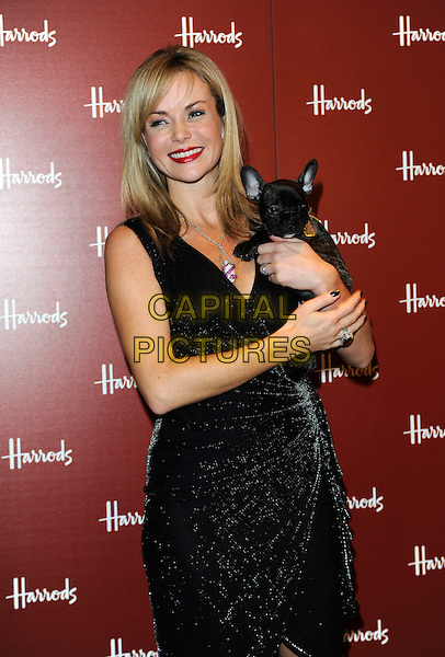 AMANDA HOLDEN.opens Harrods Winter Sale, wearing a black Temperley dress.Knightsbridge, London, England, UK,.26th December 2009.half length holding puppy dog animal sleeveless wrap necklace red lipstick smiling make-up ring lurex.CAP/FIN.©Steve Finn/Capital Pictures.