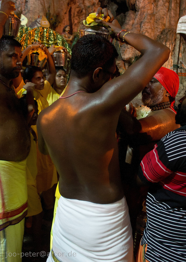 man carrying metal pot with holy milk while Thaipusam ceremonies inside Batu Caves, Kuala Lumpur, Malaysia, 2012. . Thaipusam ceremonies, celebrated by tamile Hindu community in Malaysia, take place  in Sanctuary of Batu Caves at the border of Kuala Lumpur, each year around end of January or beginning of February, according to Hindu moon calendar. The event is paying hommage to Lord Murugan, a spirit or god created by Shiva to lead the army of gods against the army of evil demons, finally defeating the evil spirits. There are many ways to present offerings or sacrifices for this major religious event. Devotees mortify their bodies by carrying heavy kavaris with spears fixed in their skin or fruits, flowers and little post with holy milk fixed with hooks in their skin, ascending the stairways to the sanctuary in trance, `followed by assistant  taking care and musicians playing loud and fast rhythmic trance music.  Many families shave their head in a ritual before ascending the stairways, as part of rituals to obtain salvation for their ancestors.