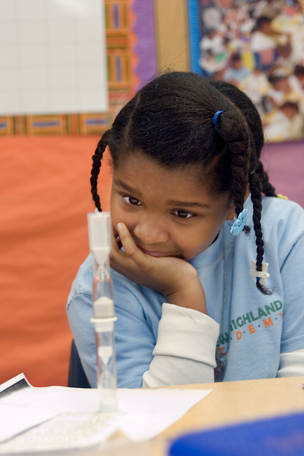 Oakland CA 2nd grader absorbed in timing friend's reading work in class, using egg timers