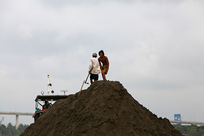 Two men stand atop a barge loaded with dirt in the Mekong Delta near My Tho, Vietnam. Oct. 3, 2011.