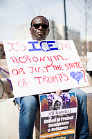 "Simon Sakpo, 50, of Brockton, Mass., holds a sign reading ""Is ICE an acronym...or just the state of Trump's [heart]?"" during a rally in support of immigrants' rights outside Brockton City Hall after rumors of an Immigration and Customs Enforcement (ICE) raid traveled around the community in Brockton, Massachusetts, USA. The rally was organized in part by the Coalition for Social Justice. Rumors of the ICE raid went viral within the community after State Representative Michelle DuBois (D-10th Plymouth District) posted a warning about the supposed raid on Facebook and that undocumented immigrants should not go outside. Sakpo is originally from Togo in West Africa."