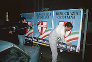 "April 27, 1990, Rome, Italy. Photographing for the book ""One day in the life of Italy"", this is an exploration of Rome. At 5am, in Lungotevere, political supporter are tacking posters in the street for Christian Democracy Libertas."