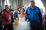 "© Joel Goodman - 07973 332324. 06/08/2017 . Macclesfield , UK . DEBBIE TIDESWELL is lead down the isle at the wedding ceremony for Debbie and Andrew Tideswell , 47 and 56 respectively, from Northwich, ""officiated"" by ""Revd Duncan Pritchard"" at an inflatable church . The couple met in the queue at the festival last year . The Rewind Festival , celebrating 1980s music and culture , at Capesthorne Hall in Siddington . Photo credit : Joel Goodman"