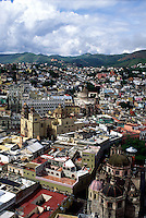 Aerial view of Colorful Mexican cityscape, puffy clouds, mountains in background #5828. Guanajuato, Mexico.