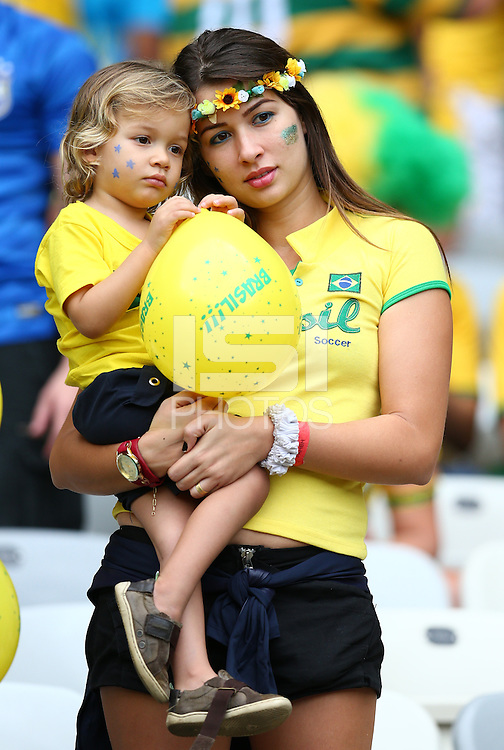 A young Brazil fan and her mother look dejected in the stands