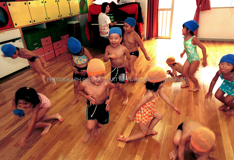 7/31/01?Tokyo, Japan..Children at the government funded Minami Azabu Day Care Center dance while a staff member plays the piano...All photographs ©2003 Stuart Isett.All rights reserved.This image may not be reproduced without expressed written permission from Stuart Isett.