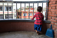 Sujal Tamang (2) looks out from the balcony of his aunt's apartment on the 5th floor in Jorpati, Kathmandu, Nepal on 2 July 2015. Sujal was buried under the rubble of his collapsed house for 36 hours before rescuers found him injured with a broken leg next to his mother who was killed on the spot. Photo by Suzanne Lee for SOS Children's Villages