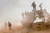 Men search a destroyed tank, blown up during an air strike against pro Gaddafi forces by the French military while enforcing a no fly zone over Libya. On 17 February 2011 Libya saw the beginnings of a revolution against the 41 year regime of Col Muammar Gaddafi.