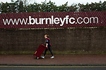 A programme seller on Harry Potts Way outside the stadium before Burnley hosted Everton in an English Premier League fixture at Turf Moor. Founded in 1882, Burnley played their first match at the ground on 17 February 1883 and it has been their home ever since. The visitors won the match 5-1, watched by a crowd of 21,484.