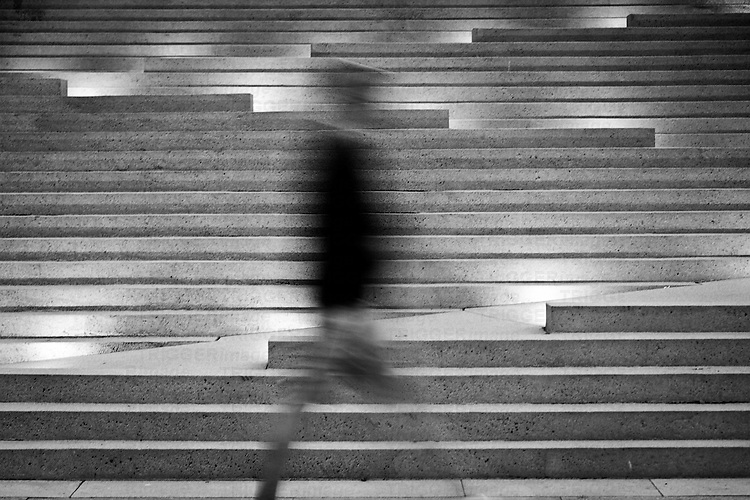 A man in blurred motion walking across lit stairs at Robson Square.