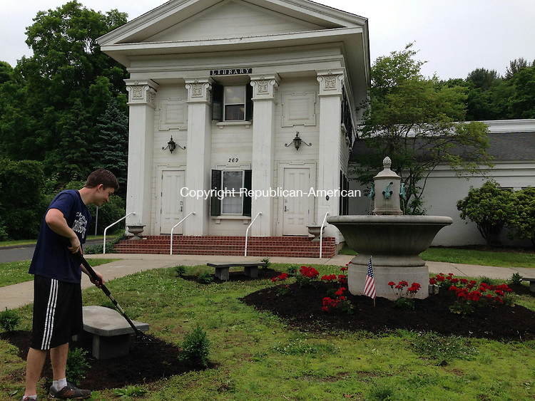 WOODBURY, CT - 9 June 2014 - 1060914RH01 - 17-year-old Woodbury resident Sam Hemmingstad tills mulch at the base of one of four benches he installed around a fountain outside Woodbury Public Library as part of an Eagle Scout project. Hemmingstad raised about $450 to finance the project. Rick Harrison Republican-American