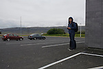 A tourist waits for transportation at a gas station at the entrance to Hveragerði, a small town and popular tourist destination in Iceland.