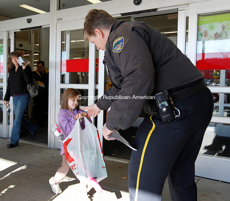 Southbury, CT- 04, December 2010-120410CM02 Southbury Police Officer, Kevin Burns receives a donated Christmas gift from Olivia Fonovic, 5, of Southbury Saturday morning outside the K-Mart in Southbury Plaza. The Southbury Police Department was outside collecting gifts for the Southbury Needy Fund.  All toys collected will go to children in the community.   Christopher Massa Republican-American
