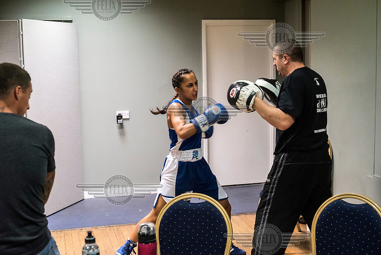 Harvinder Jutte, a female 'white collar boxer', prepares for her fight at the 'Carpe Diem' event at London Irish Centre with her trainer. <br /> <br /> 'White-collar boxing' is a growing phenomenon amongst well paid office workers and professionals and has seen particular growth in financial centres like London, Hong Kong and Shanghai. It started at a blue-collar gym in Brooklyn in 1988 with a bout between an attorney and an academic and has since spread all over the world. The sport is not regulated by any professional body in the United Kingdom and is therefore potentially dangerous, as was proven by the death of a 32-year-old white-collar boxer at an event in Nottingham in June 2014. The London Irish Centre, amongst other venues, hosts a regular bout called 'Carpe Diem'. At most bouts participants fight to win. Once boxers have completed a few bouts they can participate in 'title fights' where they compete for a replica 'belt'.