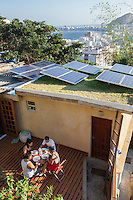 Estrelas da Babilonia eco-guesthouse & bar at the top of Favela Morro da Babilonia in Leme neighborhood – solar panels for supplying own necessity of electricity –  view of Copacabana beach, Rio de Janeiro, Brazil.