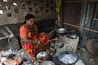 Bangladesh, Jhenaidah. Chaklapara sweeper colony. Most of these people living in this slum are Dalit Hindu, or the untouchable caste working as sweepers and toilet cleaners. There are about 5.5 million Dalit across the country, they are most neglected caste in their society. Woman cooking over clay oven.