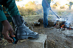 Anti-poaching scout cleaning shoes at breakfast before deployment, Kafue National Park, Zambia