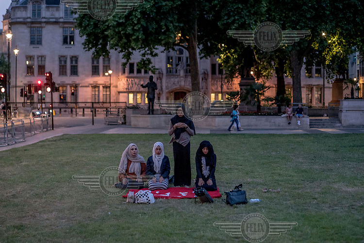 A group of women pray during a vigil outside the Houses of Parliament for the victims of the Grenfell Tower fire.