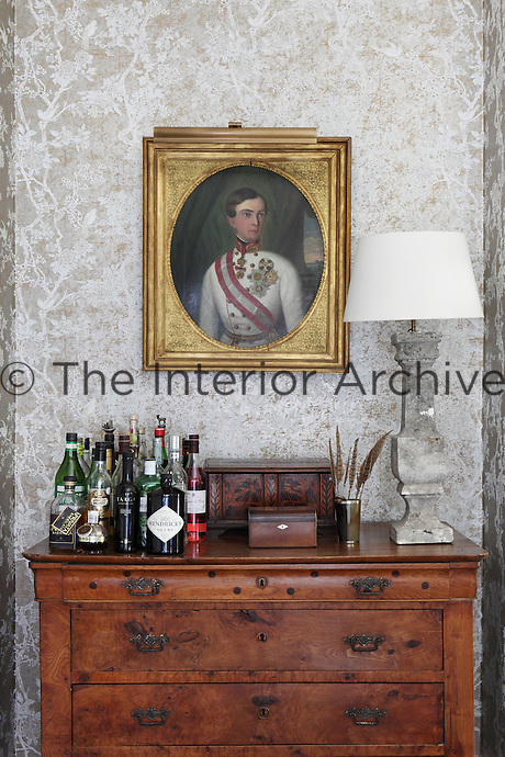 The tarnished finish of the silver wallpaper provides a complimentary backdrop to an antique portrait in the dining room
