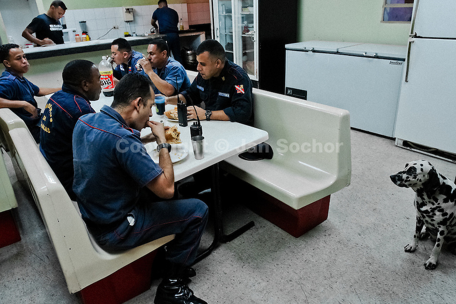 Venezuelan paramedics, members of the Caracas emergency squad, eat dinner before their 24-hour shift in Caracas, Venezuela, 24 June 2006.