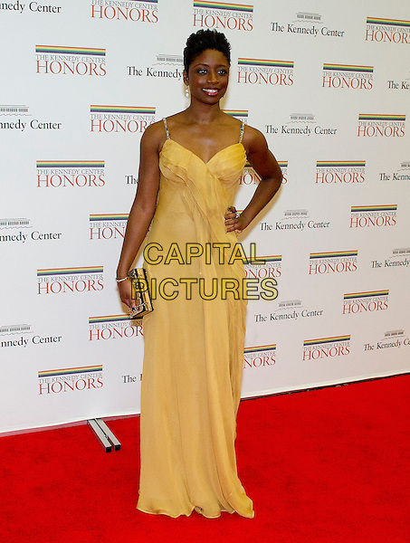 Montego Glover arrives for the formal Artist's Dinner honoring the recipients of the 2012 Kennedy Center Honors hosted by United States Secretary of State Hillary Rodham Clinton at the U.S. Department of State. The 2012 honorees are Buddy Guy, actor Dustin Hoffman, late-night host David Letterman, dancer Natalia Makarova, and the British rock band Led Zeppelin - Robert Plant, Jimmy Page, and John Paul Jones.  .Washington, DC .December 1st, 2012.full length yellow dress hand on hip gold clutch bag.CAP/ADM/CNP/RS.©Ron Sachs/CNP/AdMedia/Capital Pictures.