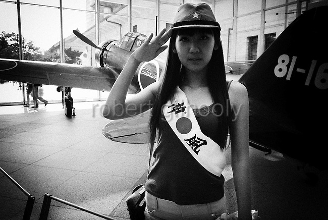 """A woman dressed in military garb and a sash that reads """"Kamikaze"""" salutes next to a war-time military aircraft at a museum in the grounds of Yasukuni Shrine in Tokyo, Japan..Every year on August 15, the day Japan officially surrendered in WWII, tens of thousands of Japanese visit the controversial shrine to pay their respects to the 2.46 million war dead enshrined there, the majority of which are soldiers and others killed in WWII and including 14 Class A convicted war criminals, such as Japan's war-time prime minister Hideki Tojo. Each year speculation escalates as to whether the country's political leaders will visit the shrine, the last to do so being Junichiro Koizumi in 2005. Nationalism in Japan is reportedly on the rise, while sentiment against the nation by countries that suffered from Japan's wartime brutality, such as China, has been further aggravated by Japan's insistence on glossing over its wartime atrocities in school text books..Photographer:Robert Gilhooly.Photographer:Robert Gilhooly"""