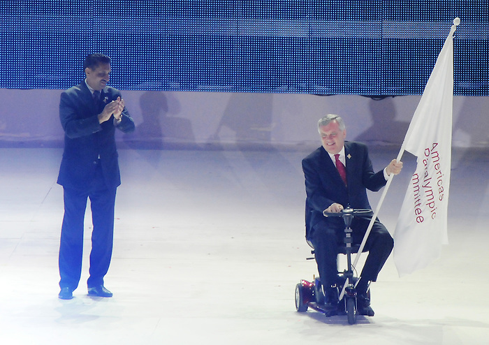 November 20 2011 - Guadalajara, Mexico:  Ontario's Lieutenant Governor Honorable David Onley with the Americas Paralympic Committee flag as Minister of Sport Bal Gossal looks on during Closing Ceremonies for the 2011 Parapan American Games at the Telmex Athletics Stadium in Guadalajara, Mexico.  Photos: Matthew Murnaghan/Canadian Paralympic Committee