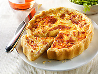 Quiche Loraine in a lunch time setting with a cut slice