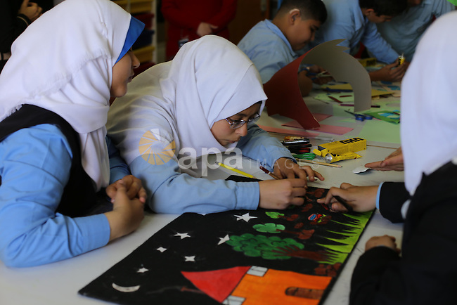 Palestinian deaf children draw paintings in class as part of the rehabilitation of deaf children after the recent Israeli war on Gaza Strip, in Gaza city on March 16, 2014. Photo by Mohammed Asad