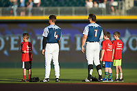 Charlie Tilson (4) and Daniel Palka (7) of the Charlotte Knights are joined on the field by several young fans for the playing of the National Anthem prior to the game against the Indianapolis Indians at BB&T BallPark on April 27, 2019 in Charlotte, North Carolina. The Indians defeated the Knights 8-4. (Brian Westerholt/Four Seam Images)