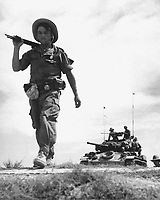 A French Foreign Legionnaire goes to war along the dry rib of a rice paddy, during a recent sweep through communist-held areas in the Red River Delta, between Haiphong and Hanoi.  Behind the Legionnaire is a U.S. gifted tank.  Ca.  1954.  Pix.  (USIA)<br /> EXACT DATE SHOT UNKNOWN<br /> NARA FILE #:  306-PS-54-10014<br /> WAR & CONFLICT BOOK #:  382
