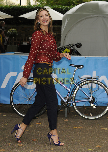 Kelly Brook .Sky Ride London photocall in front of  Buckingham Palace the  Mall, London, 4th September 2011..full length red print long sleeve top blouse  navy blue trousers sandals shoes black side walking  polka dot smiling  brown tan belt .CAP/CAN.©Can Nguyen/Capital Pictures.