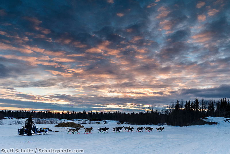 Jason Campeau leaves the Nikolai checkpoint as the sun sets during Iditarod 2016.  Alaska.  March 08, 2016.  <br /> <br /> Photo by Jeff Schultz (C) 2016 ALL RIGHTS RESERVED