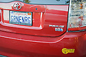 A rear view of Toyota Prius with a 'GRNENRG' (Green Energy) license plate and a clean air vehicle sticker. Mountain View, California, USA