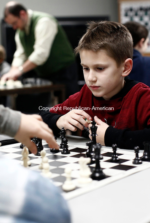 Thomaston, CT- 27 January 2014-012714CM04- Nathan Kowalski, 8, of Thomaston, contemplates a move as opponent Salvatore Treglia, 11, of Thomaston moves a piece during a chess class at the Thomaston Library on Monday.  The class was put on by chess instructor, Alexander Lumelsky, who was born in St. Petersburg, Russia, and has been playing chess since the age of 4.  Now residing in West Hartford, Lumelsky, is the coach of Bugbee Elementary School chess team in West Hartford.  Lumelsky was teaching the kids opening ideas, which he said would help their opening moves be more effective.     Christopher Massa Republican-American