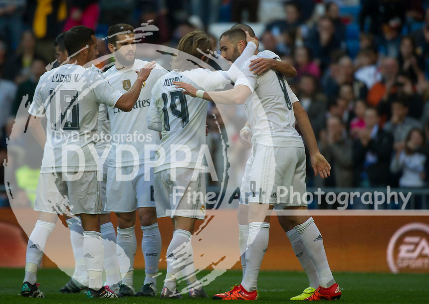 Real Madrid's French forward Karim Benzema (R) celebrates with teammates after scoring