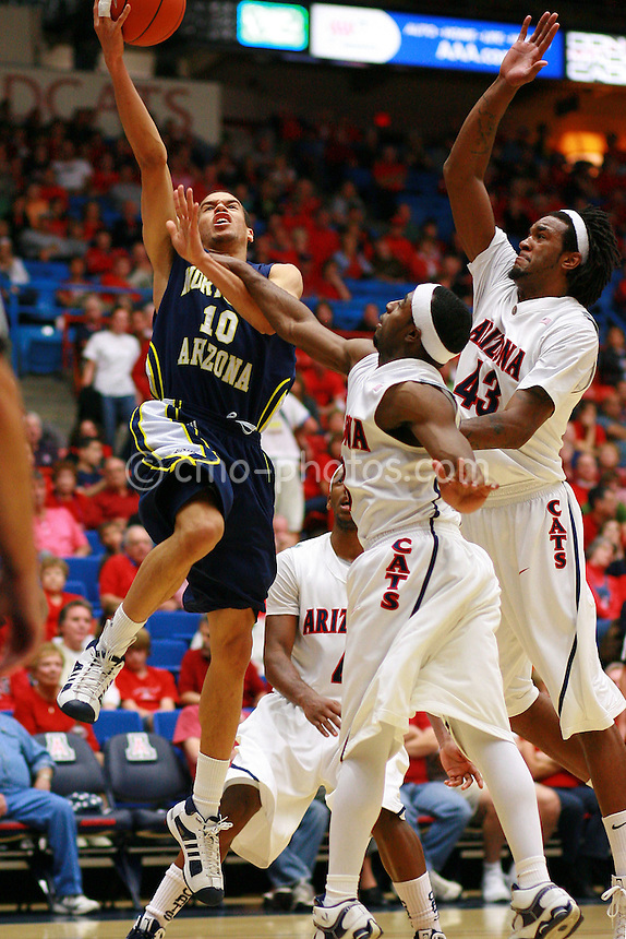 Nov 30, 2008; Tucson, AZ, USA; Northern Arizona Lumberjacks guard Cameron Jones (10) goes up for a shot while Arizona Wildcats guard Nic Wise (13) and forward Jordan Hill (43) try to defend it in the first half of a game at the McKale Center.  Arizona won the game 74-57.