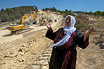 A Palestinian woman cries out to Allah following the destruction of her olive trees at a construction site for Israel's controversial West Bank barrier at the village of Al Walaja near Bethlehem on 08-06-2010.