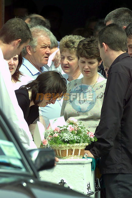 marie Curtis leans on the coffin of her son garry before its put into the herse for the long walk to the Graveyard in Nobber Co Meath..Picture Fran Caffrey Newsfile.